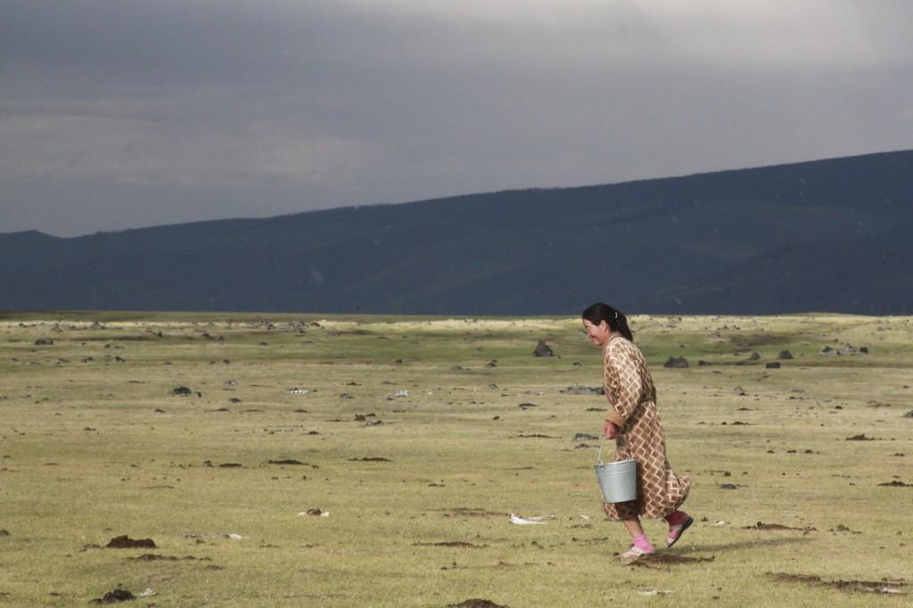 Bäuerin läauft durch den Hagel über die Prärie